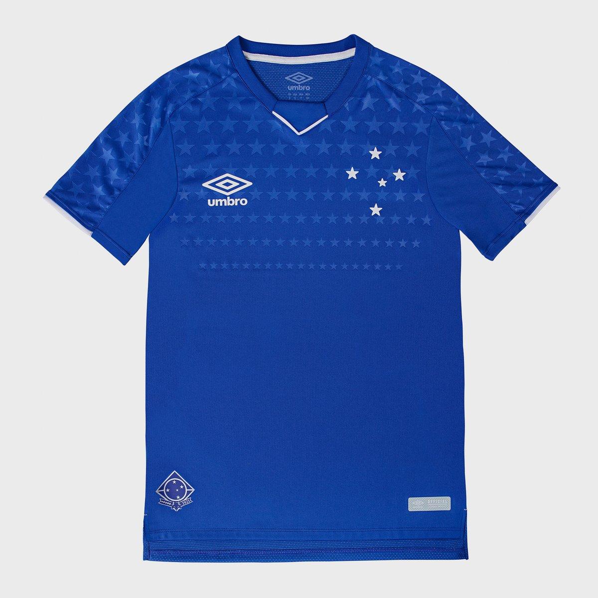 """65358ee6bea83 A nova camisa do Cruzeiro é predominantemente azul e com uma sequência de  estrelas no peito e nas mangas em marca d agua. A gola é em """"V"""" com um  traçado em ..."""